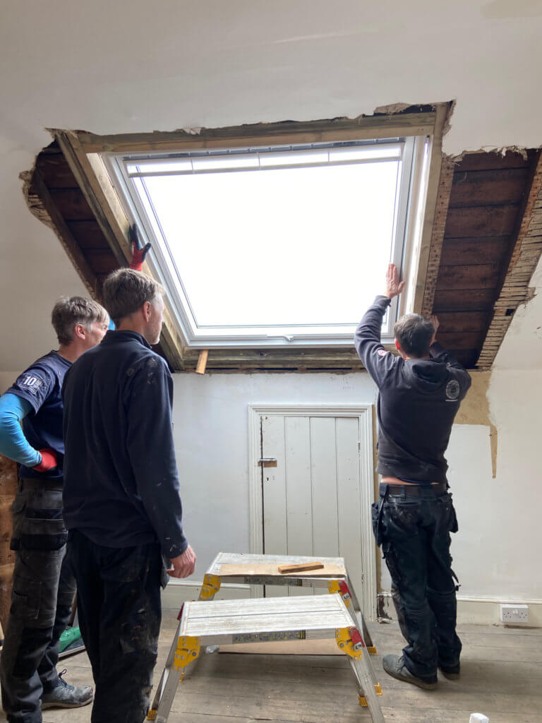 Builders putting a VELUX frame in the roof