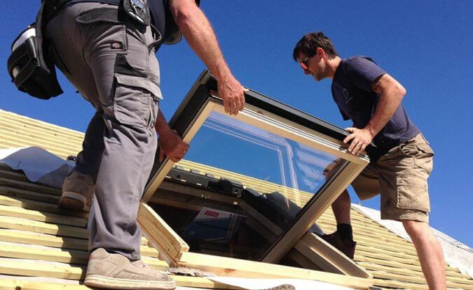 Two builders installing a VELUX Window