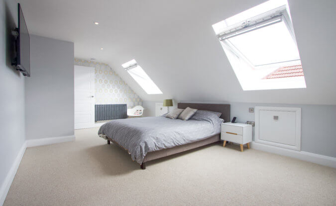 Two open VELUX windows in a bedroom