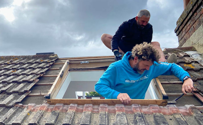 Two men replacing a VELUX window on a roof.