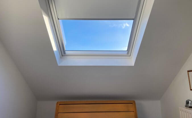 velux directly over a bed with blue sky